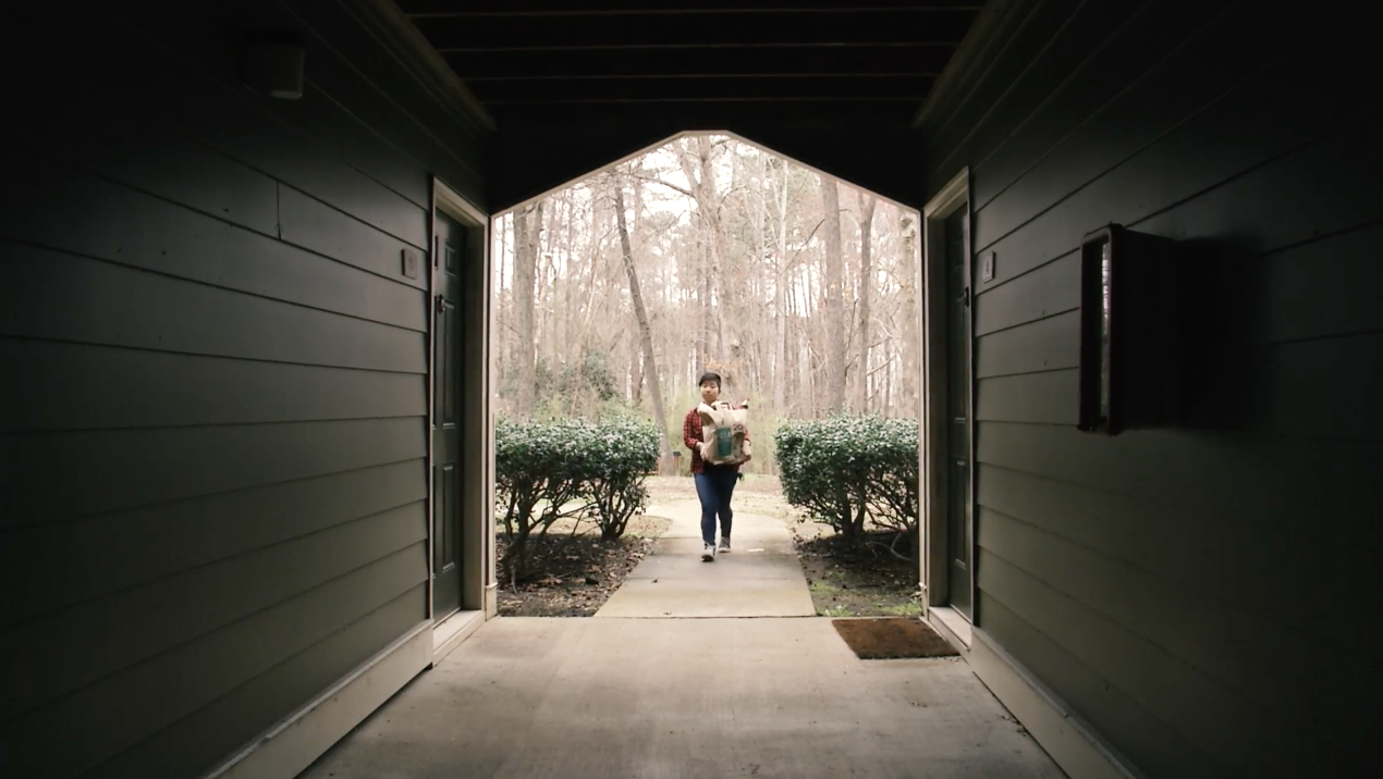 Outdoor breezeway with a person standing in it, with dramatic lighting